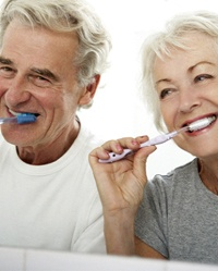 Happy senior couple brushing teeth to care for dental implants