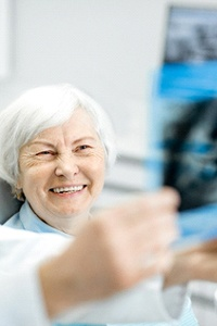 Happy senior patient during dental implant recall visit