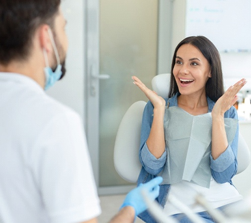 Young woman smiling at a dental professional and happy about the results of her smile