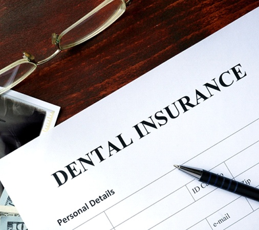 "A piece of paper that reads ""Dental Insurance"" along with a pair of glasses, X-ray, money, and a pen"