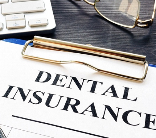 Dental insurance paperwork with computer, pen, and glasses